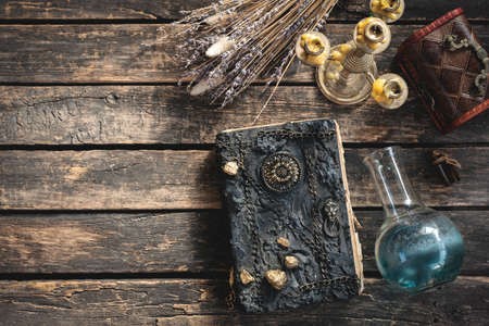 Spell book and magic potion on the old table. The witchcraft.