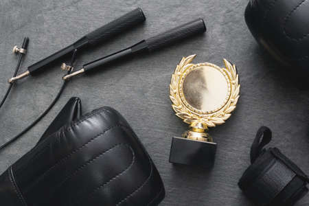 Golden medal, boxing gloves, skipping rope on the black table background. 写真素材