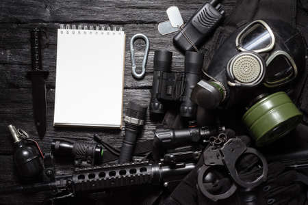 Military equipment list template concept. Airsoft equipment on the black table background.