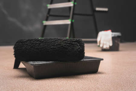 Paint roller, paint and step ladder on the black color wall background.