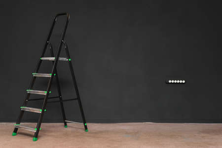 Black step ladder on the black color wall background.