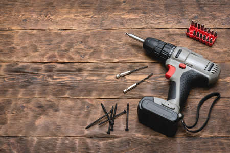 Screwdriver drill and screws on the brown wooden workbench background with copy space.