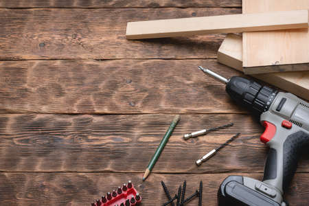 Cordless screwdriver, screws, pencil and wooden bars on the brown wooden workbench background with copy space.