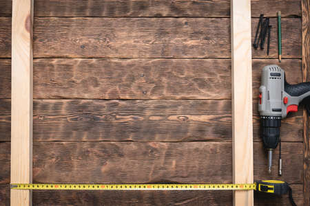 Screwdriver, screws, meter, wooden bars on the carpenter workbench background flat lay.