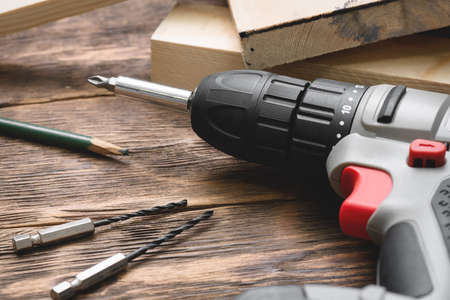 Screwdriver drill on the wooden workbench background close up.