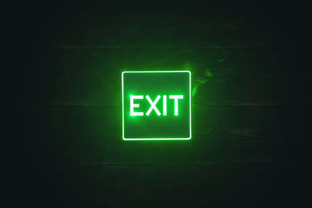 Exit sign light on the wooden wall background.