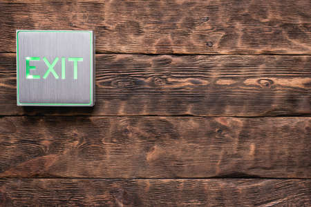 Exit sign light on the wooden wall background with copy space.