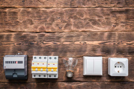 Electric meter, switch breaker, light bulb and outlet on the brown wooden wall background with copy space. 写真素材