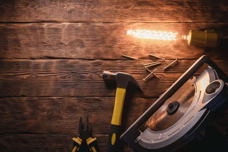 Circular saw, hammer, pliers and wooden bars on the brown wooden workbench background with copy space. 写真素材