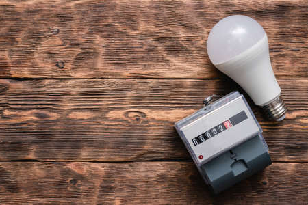 Electric meter and light bulb on the wooden background. 写真素材