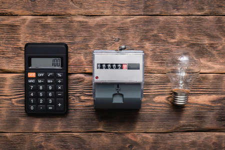 Calculator, light bulb and electric meter on the wall. Calculation of electricity costs concept.