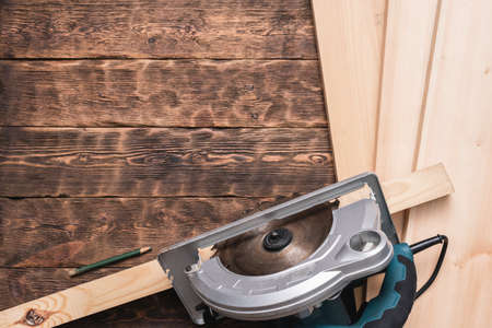 Circular saw and wooden bars on the brown wooden workbench background with copy space.