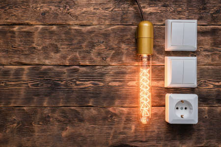 Electrical switch, light bulb and electric outlet on the brown wooden workbench background with copy space.