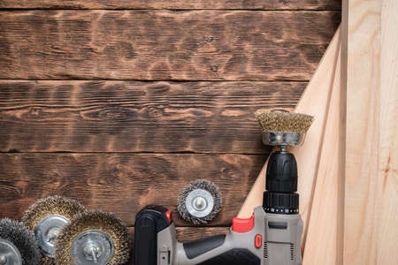 Cordless screwdriver with grinding disc and wooden bars on the wooden workbench background with copy space.