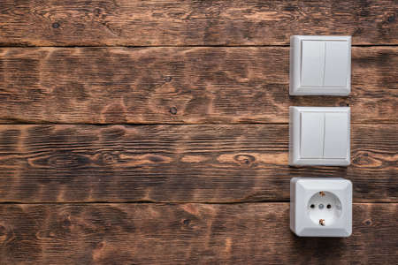 Electrical switch and electric outlet on the brown wooden workbench background with copy space.