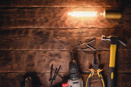 Hammer, pliers and nails in the light of lamp on the wooden workbench background top view.