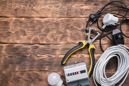Electric equipment and accessories on the brown wooden table background with copy space.