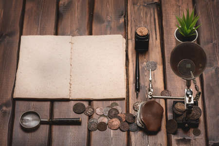 Blank page old coins catalog template, old coins and magnifying glass on the brown wooden table background.