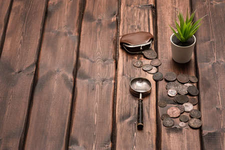 Old ancient coins and magnifying glass on the table with copy space.