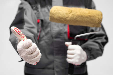 House painter with a paint roller in the hand is showing a thumbs up gesture sign.