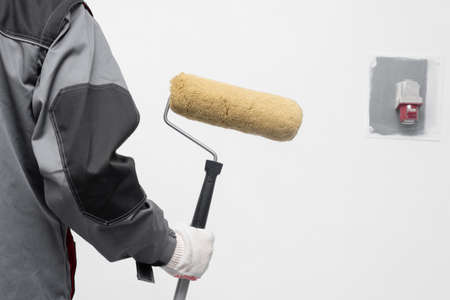House painter with a paint roller in hand on the white wall background.
