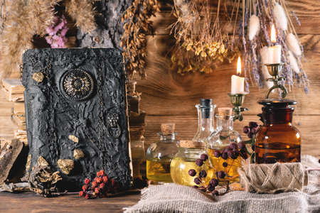 Spell book, magic potion on the witch doctor desk table background. 写真素材
