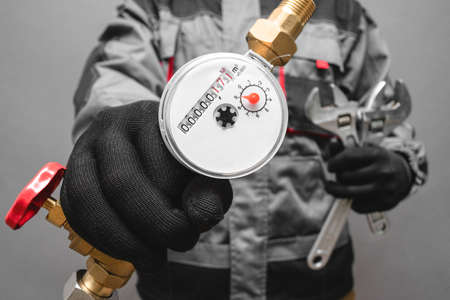 Water meter and adjustable wrench in the plumber hands close up.