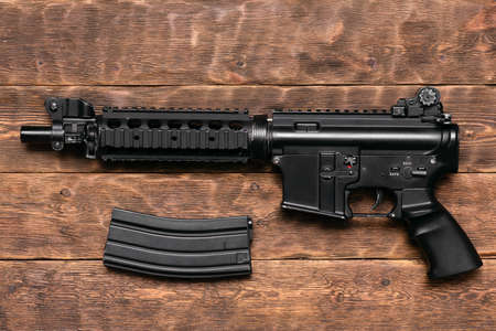 Airsoft rifle on the brown wooden table background.