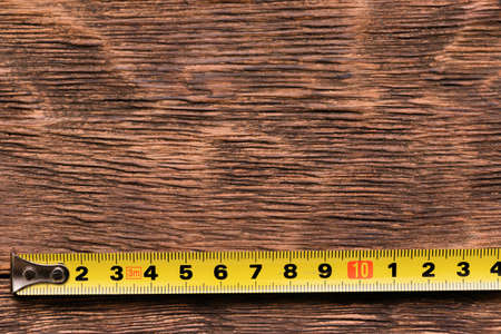 Construction tape on the brown wooden workbench background with copy space.