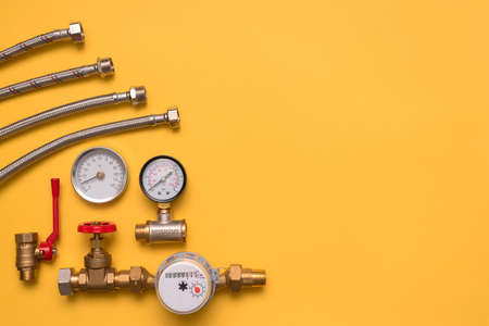 Plumbing accessories on the yellow flat lay background with copy space. Water hose, pressure meter, water thermometer and water meter.