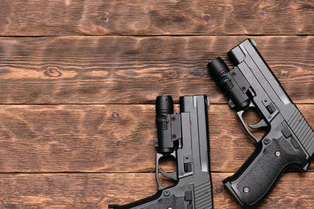 Two toy guns with laser sights on the brown wooden table background with copy space. 免版税图像