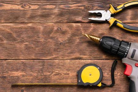 Construction tape, cordless drill and pliers on the brown wooden table background with copy space.