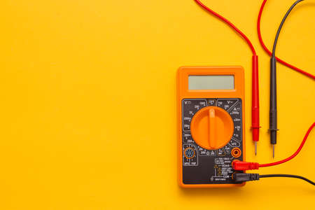 Electric multimeter on the yellow background with copy space.