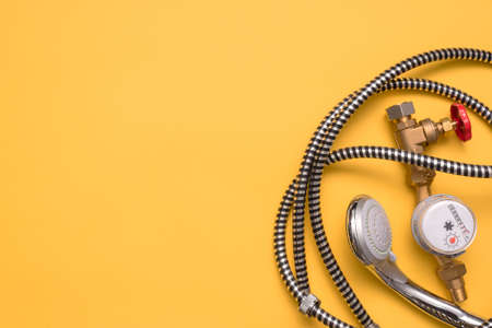 Shower head and water hose and water meter on the yellow flat lay background with copy space. 免版税图像