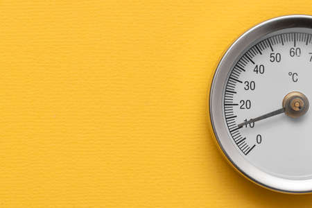 Water temperature meter on the yellow abstract background.