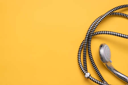 Shower head and water hose on the yellow flat lay background with copy space.