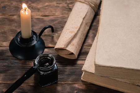 Ball pen, inkwell, parchment scroll, books and burning candle on the table close up. 免版税图像