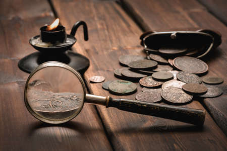 Old ancient coins and magnifying glass on the wooden desk table close up background. 免版税图像