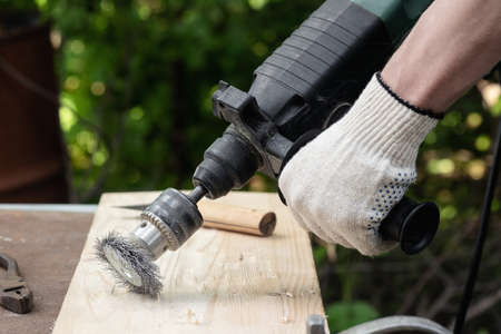 Carpenter is brushing wood by the grinding disc close up.
