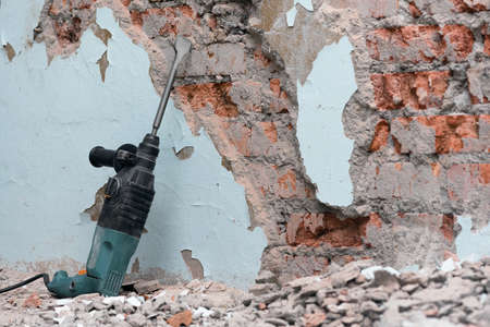 Hammer drill with chisel on the old brick wall background. Removing an old putty from the wall background. 免版税图像