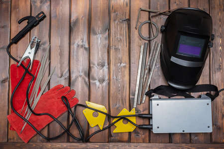 Welding flat lay background with copy space. Welding equipment on the wooden background.