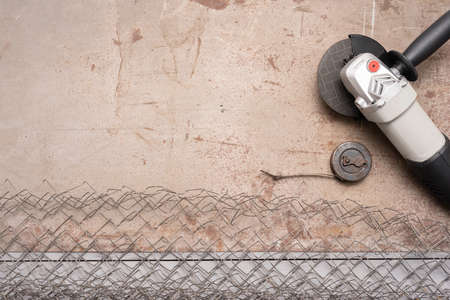 Metal pieces, circular saw, fencing net and meter on the gray background with copy space. 免版税图像