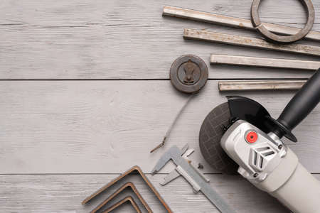 Metal pieces, circular saw and meter on the gray background with copy space.
