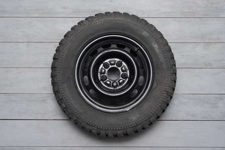 Off road mud terrain wheel on the gray flat lay background.