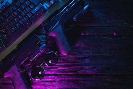 Cyberpunk concept flat lay background with copy space. Guns and computer keyboard on the table background in the neon lights.