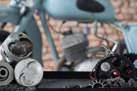 Motorcycle repairing service concept background. A car engine piston, gear and wrenches on the rack on the old garage background. Standard-Bild