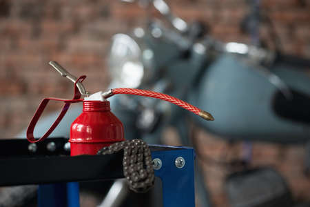 Motorcycle repairing service concept background. A red oil can on the workbench on the old garage background. 版權商用圖片