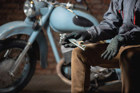 A mechanic with a wrench in hand is sitting on the broken motorbike background and is spreading his hand. Motorcycle repairing service concept. 版權商用圖片