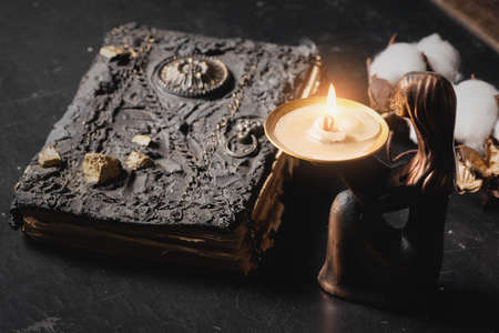 Ancient magic book and burning candle on the table close up. The witchcraft concept. 版權商用圖片