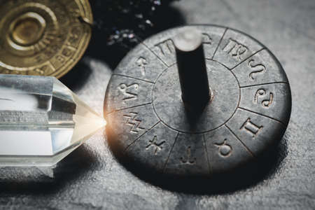 Horoscope zodiac wheel on the table close up. Aquarius sign.